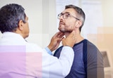 A man getting his thyroid checked.