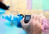 A runner pauses his workout to check his heart rate on his fitness tracker.