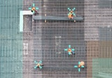 An aerial view of a construction site. Pixelated overlays target the construction workers' hard hats.
